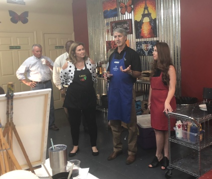 Event sponsors, Jared Gary with Assurance Financial, and Olivia Byers with Title Stream welcomes guests at the Coldwell Banker ONE fundraiser for Pat's Coats for Kids